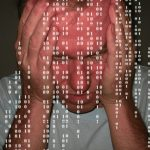 Man holding head in hands overwhelmed by computer data
